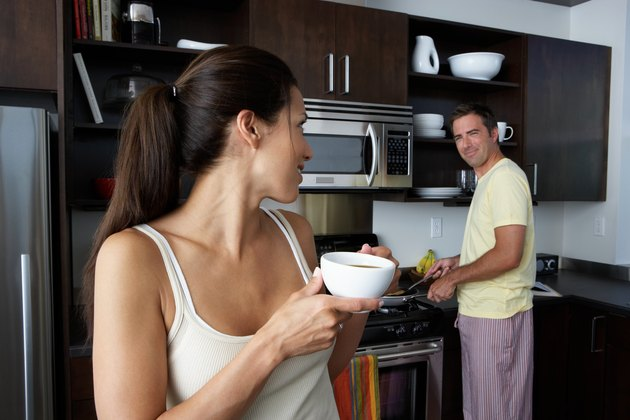 Man and woman preparing breakfast and smiling at one another