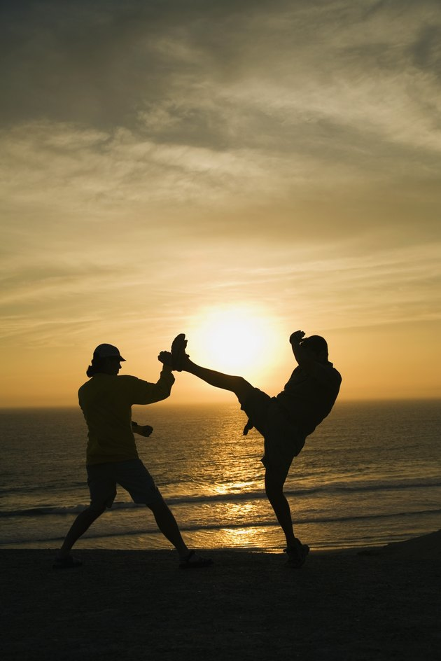 Two men fighting on a beach