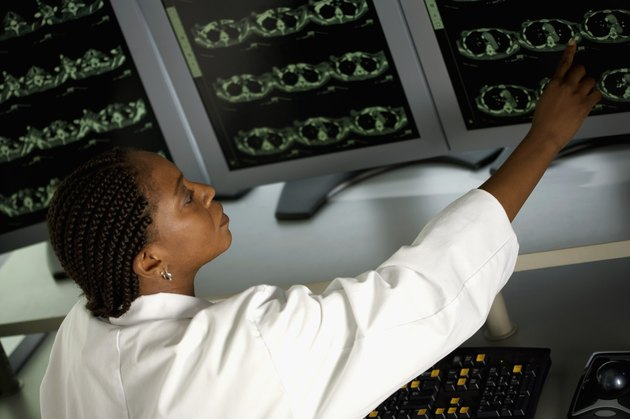 Profile of female doctor in front of MRI monitor screens