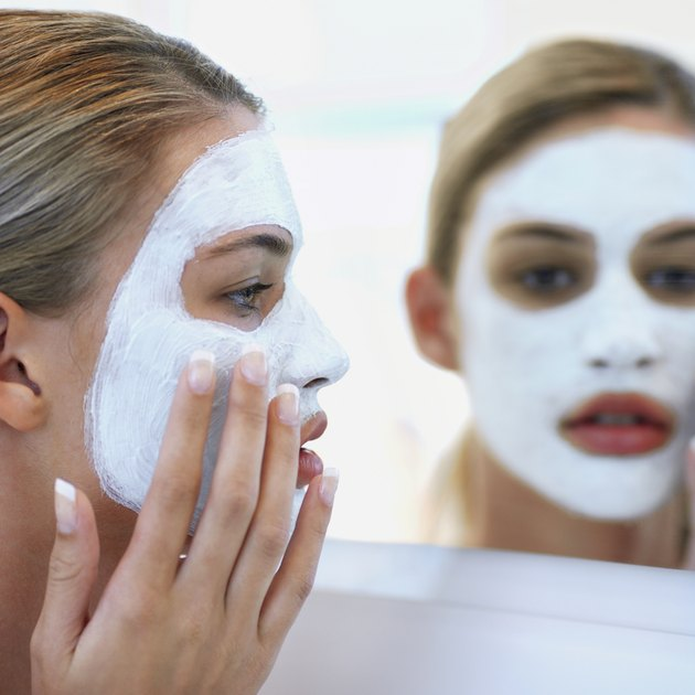 Young woman putting on face pack, reflection in mirror