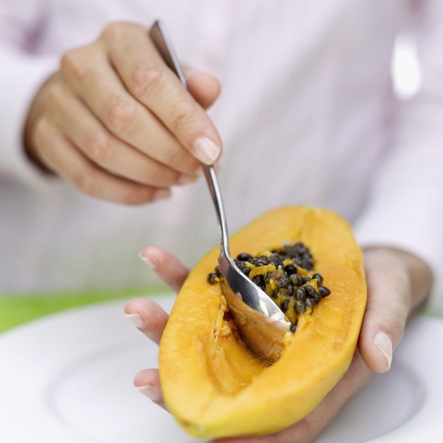 Woman's hands removing seed of a papaya with a spoon