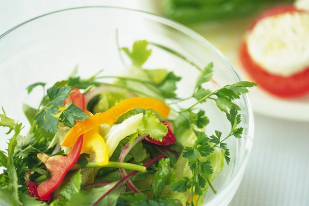 Mixed salad leaves in bowl, another salad visible in background, Differential Focus