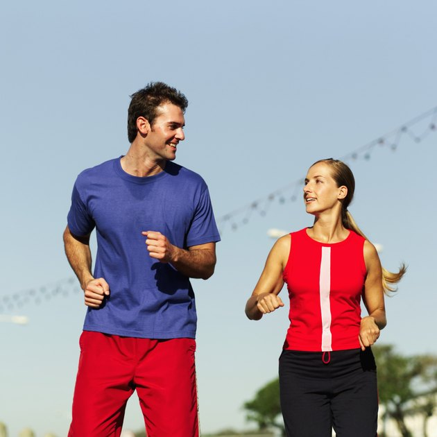 Low angle view of a young couple talking to each other while jogging