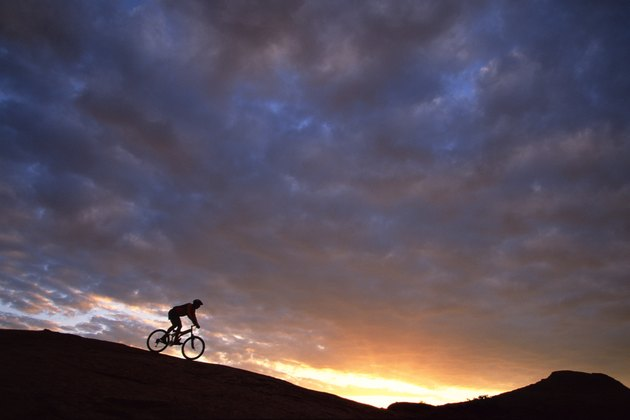Man mountain-biking on slickrock at dawn