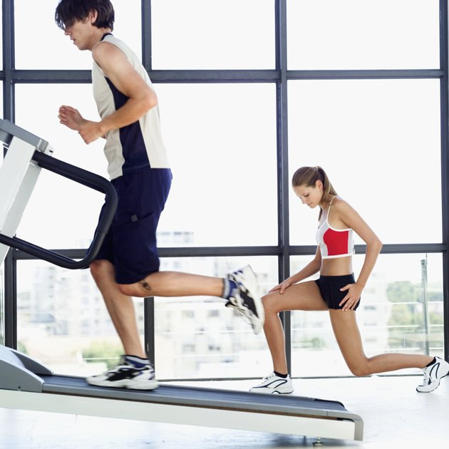 Young man running on a treadmill beside a young woman doing lunges