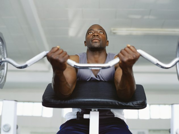 Low angle view of a mid adult man exercising in the gym with weights
