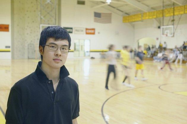 Teenage boy standing on basketball court