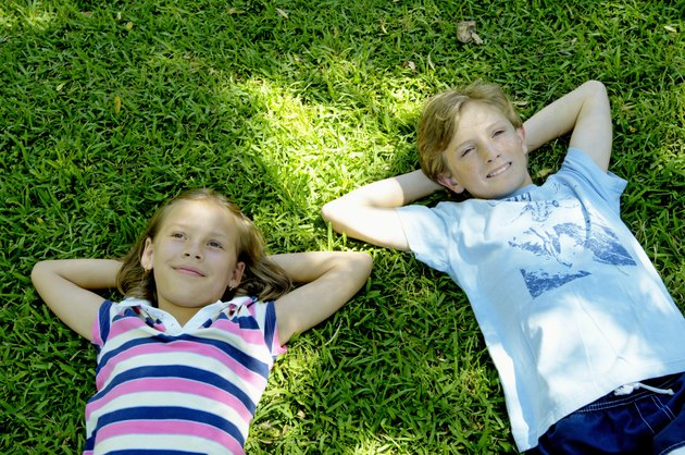 Girl and boy (9-11) lying on grass, hands behind heads, smiling