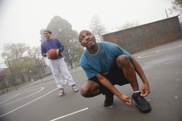 Young man lacing up basketball shoes on street court