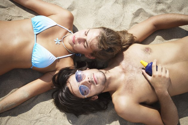 Couple lying on beach, overhead view, eyes closed