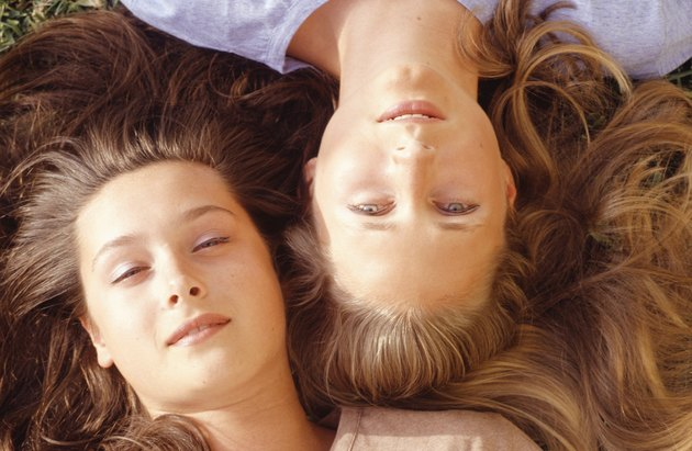 Two young women lying, portrait, overhead view, close-up
