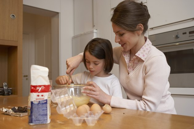 Mother helping daughter (6-8) stir cake mixture in kitchen, smiling