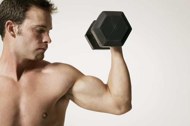 Muscular man lifting weight in studio