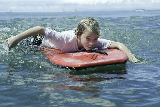 Boy (12-13), lying on bodyboard in ocean