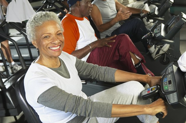 Senior women on cycling machine in gym, smiling, portrait