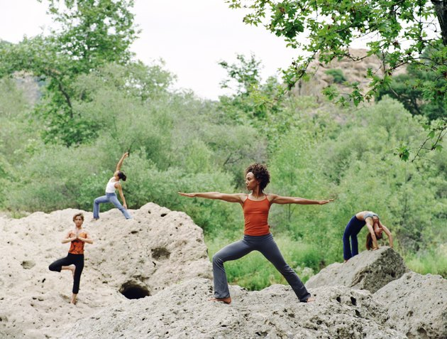 Women doing yoga positions on rocks