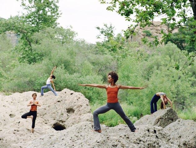Women doing yoga positions on rocks