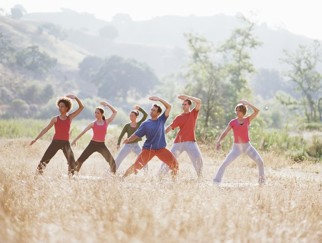 Group of people doing thai-chi pose in field