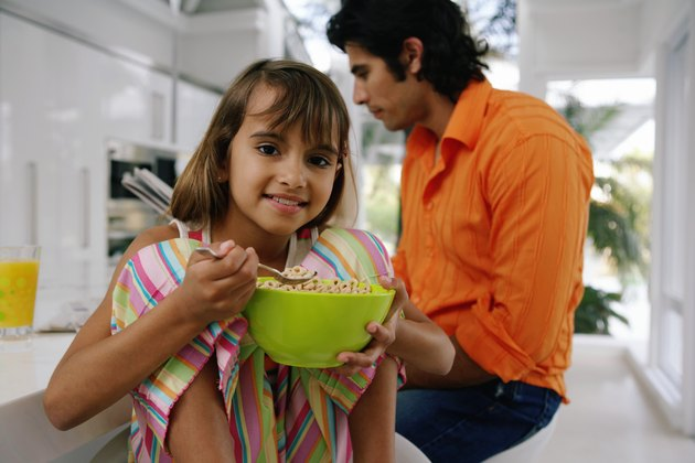 Dad with newspaper at table, girl (8-10) with bowl of cereal, portrait