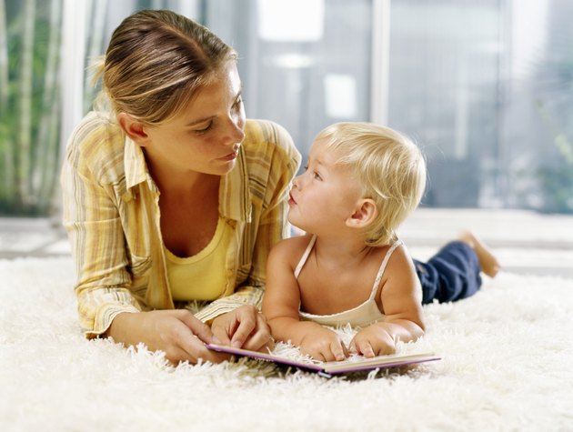 Woman and female toddler (21-24 months) lying on rug with book, looking at each other