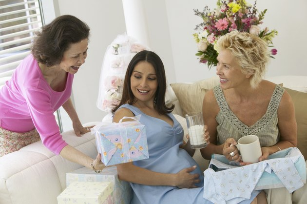 Two mature woman and pregnant woman, one handing pregnant woman gift