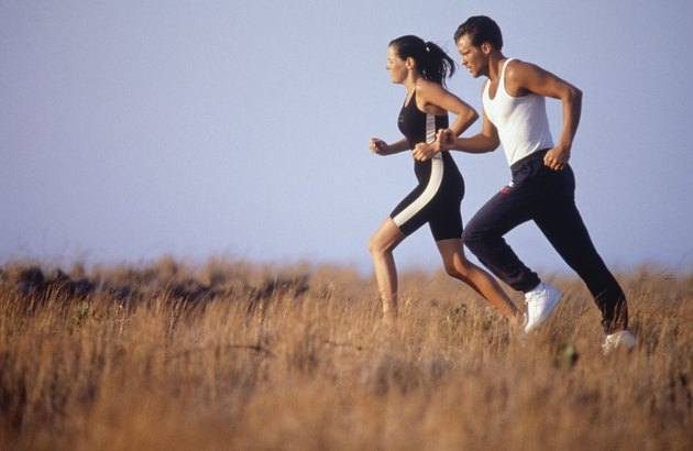 Young couple jogging in field, side view