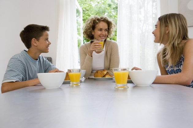 Mother, son and daughter (13-15) having breakfast together, smiling