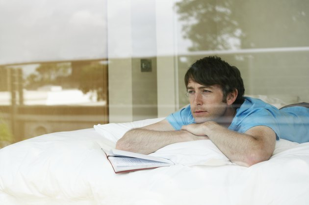 Young man lying on bed with open diary, view through window