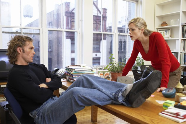 Male office worker with feet on desk, woman leaning on edge of desk