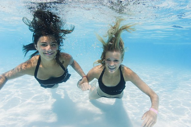 underwater lifestyle shot of two teenage female friends as they swim together in a pool