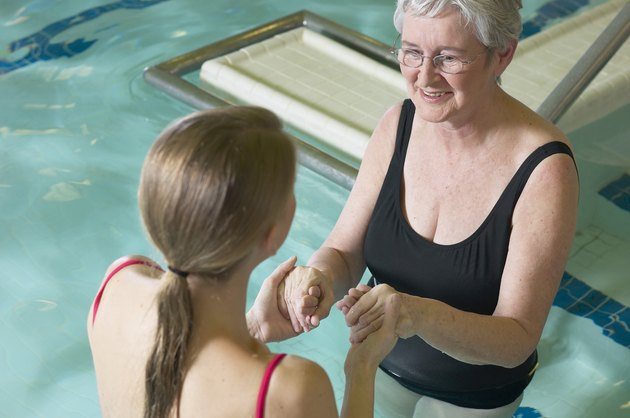 Woman in water therapy with therapist