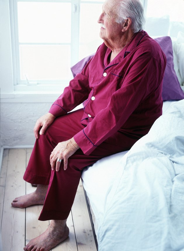 side profile of an elderly man sitting in a night suit on the bed