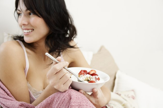 Woman Eating Strawberries, Granola, and Cream in Bed