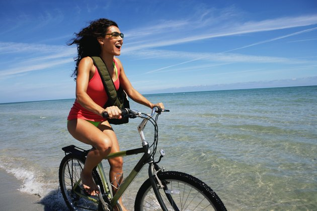 Young woman riding bicycle on beach, smiling, side view