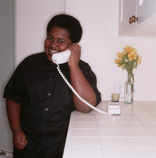 Teenage boy (16-17), talking on telephone in home, portrait
