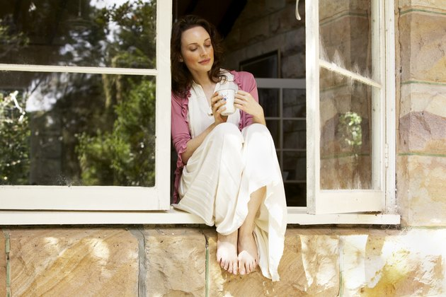 Woman sitting in window with coffee cup