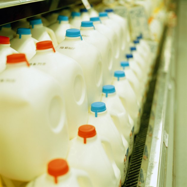 Rows of plastic milk containers in supermarket