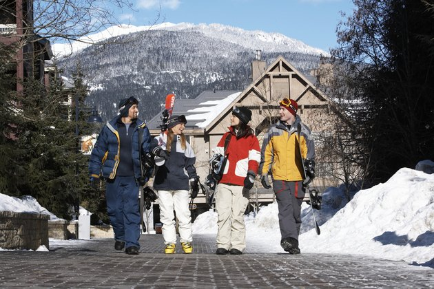Four adults with skis and snowboards walking and talking