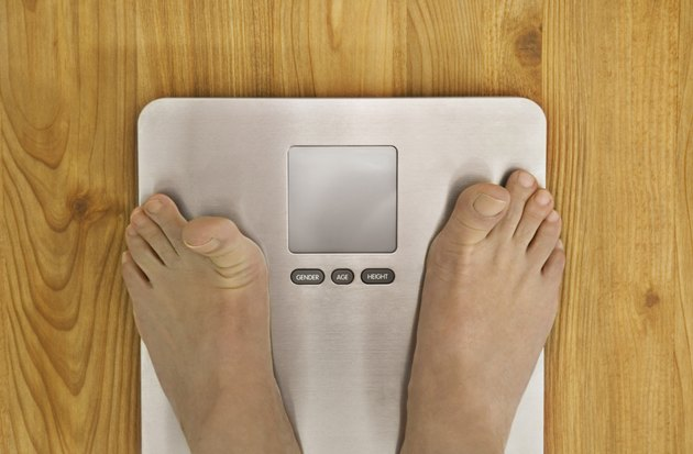 Person standing on weighing scale, low section, view from above