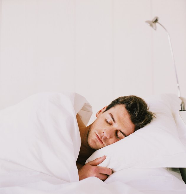Young man sleeping with duvet covering him in bed