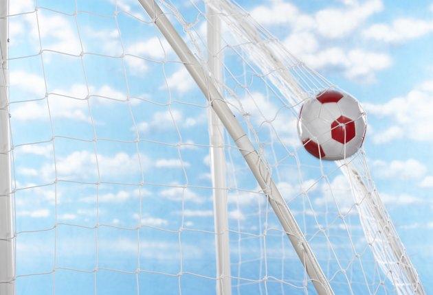 Soccer ball hitting back of net of goal