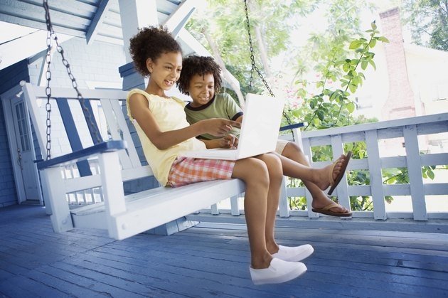 Brother and sister with laptop computer outdoors