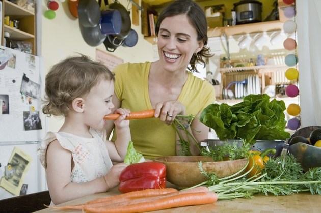 Woman and toddler in kitchen with vegetables