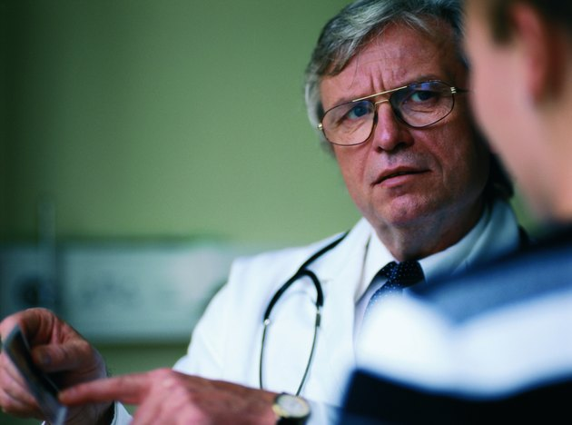Close-up of an elderly male doctor talking to a patient