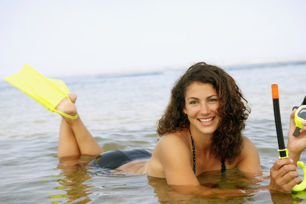 Woman with snorkel gear in water