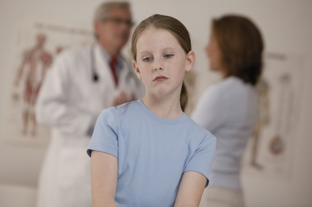 Sick girl sitting in doctor's office while mother and doctor talk in background