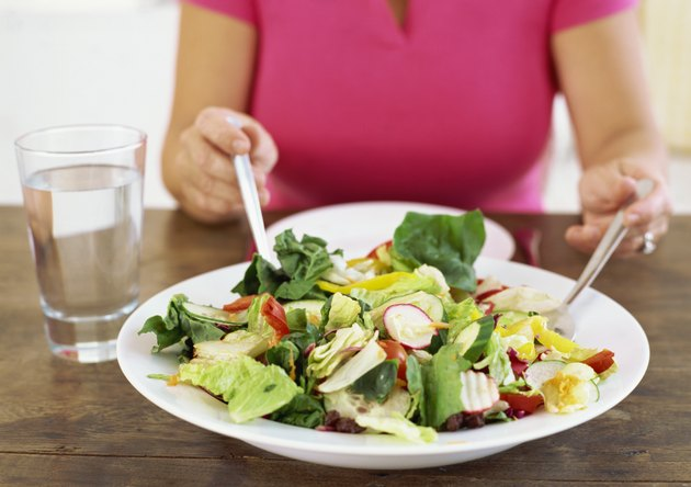 mid section view of a woman with a plate of salad on a table