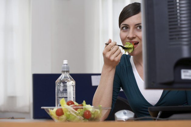 Woman eating salad at desk in office