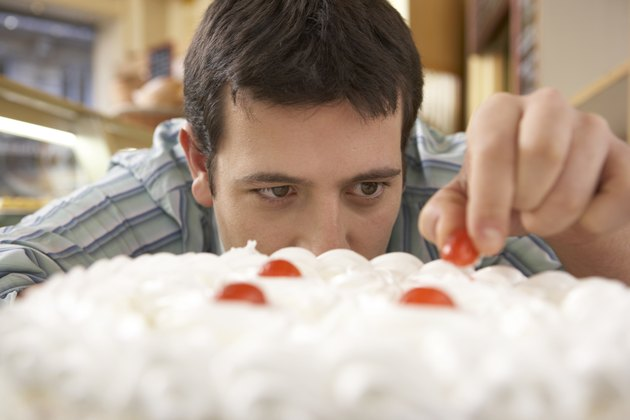 Young man putting cherry on top of cake, close-up
