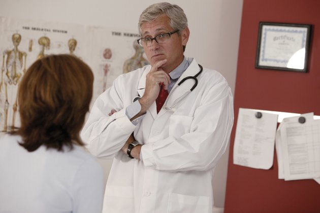 Doctor listening to woman patient during checkup